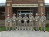 Seven officers in uniform standing in front of school entrance