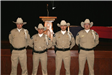 Four Honor Guards in uniform standing in front of stage