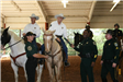 Officer receiving graduation certificate in horse arena