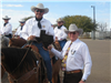 Officer on horseback holds award beside Sheriff Painter