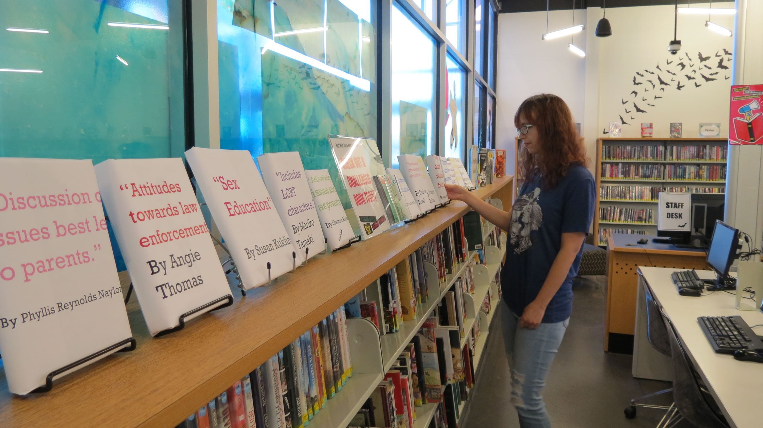 Teen looking at book display