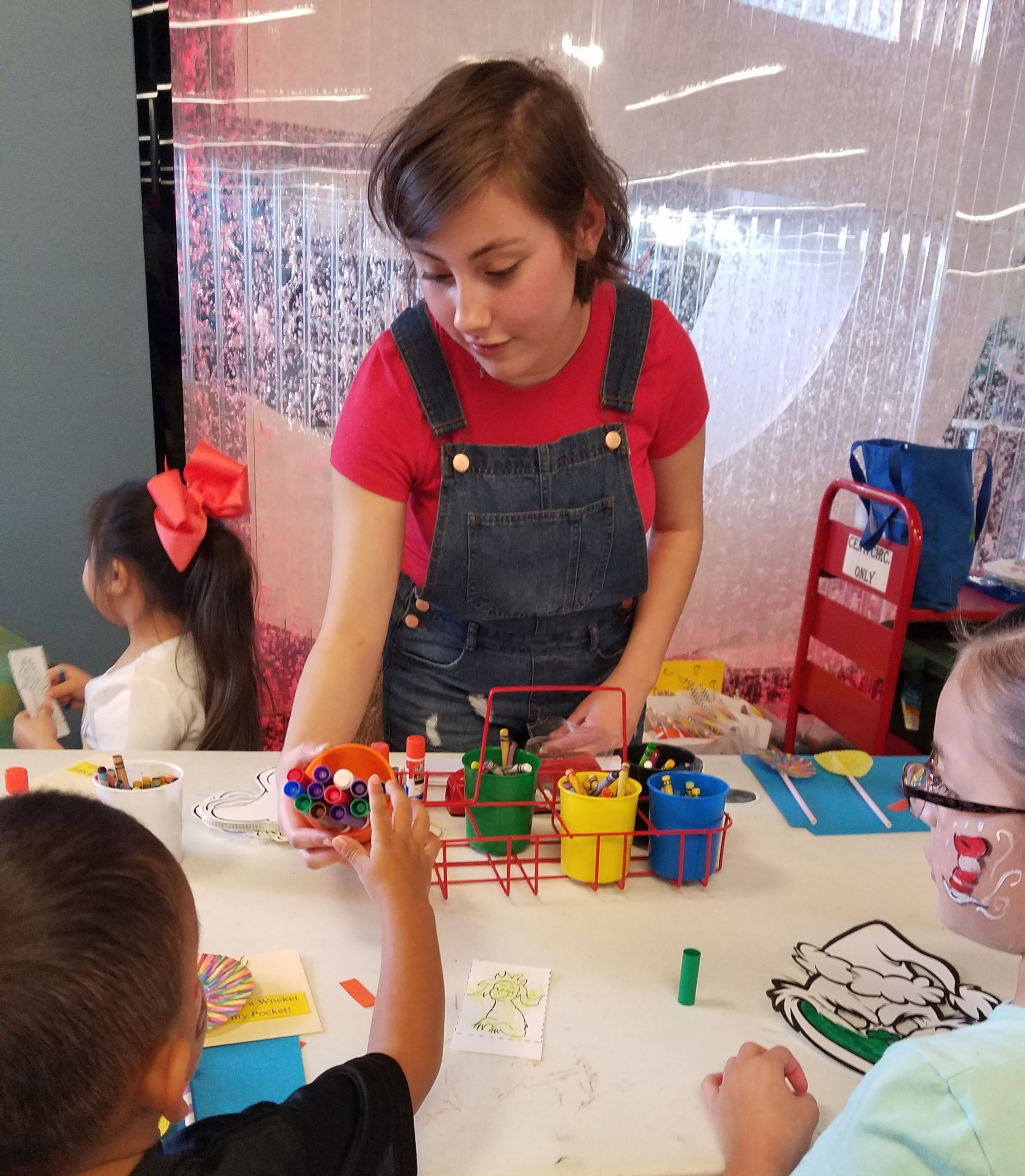 Teen girl helping children at craft table