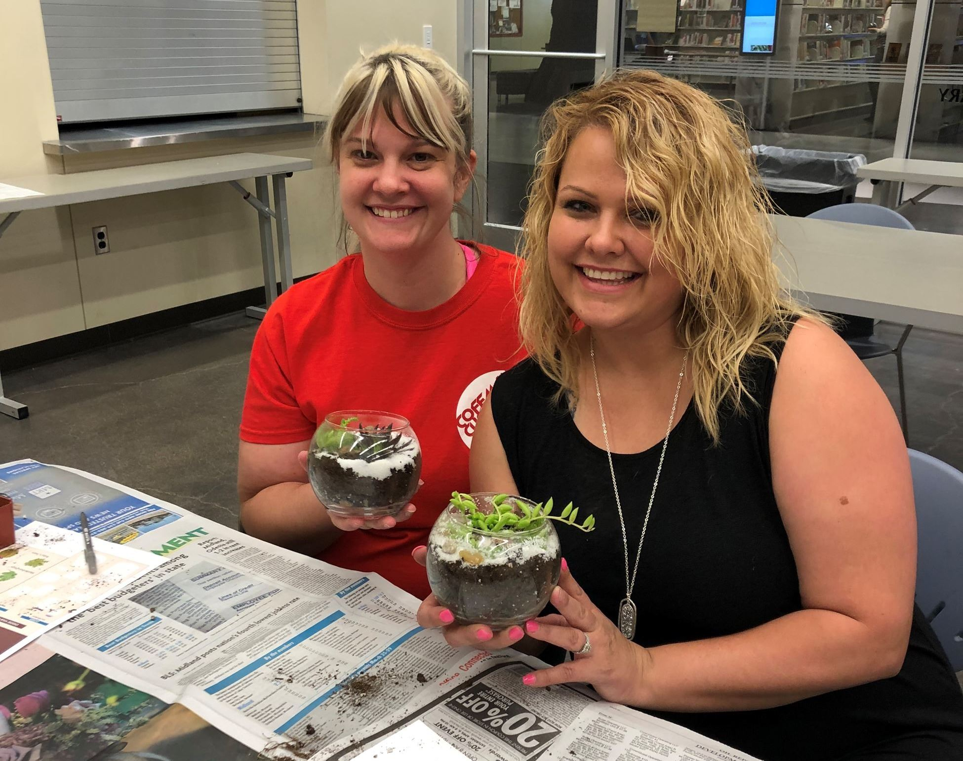 2 women holding terrariums