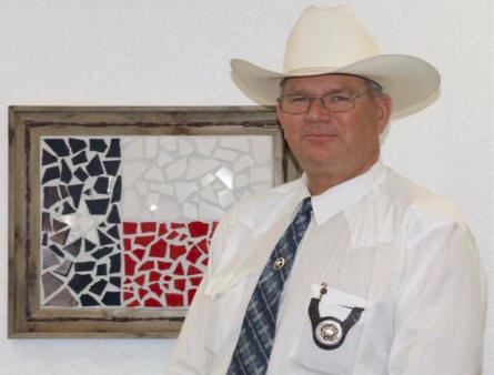 Sheriff standing with stetson hat on in front of mosaic Texas flag