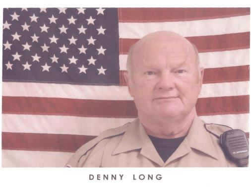 Denny Long standing in front of American flag