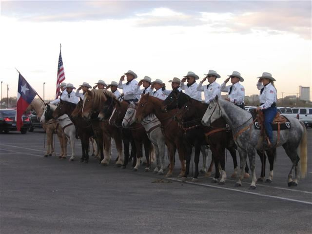 Honor guard saluting while on horseback, image from side